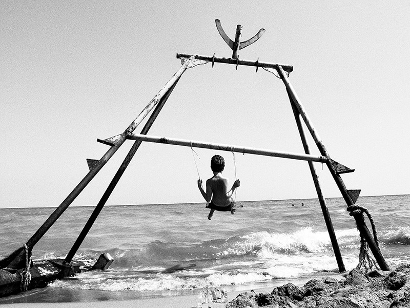 Photo: a child on a swing hanging from the remains of an immigrants' boat. - © Marco Ristuccia
